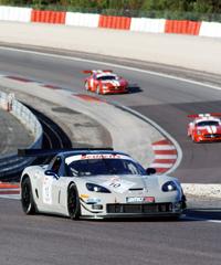Bender (Dijon) in der Corvette vor den Stucky-Brüdern (CH) auf Ferrariroten SLS-Modellen